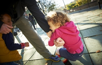 Young African American Boy and Caucasian girl cling to an adult male's arm and leg while on a playground.