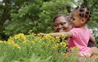 Young African American girl in the arms of her grandmother in a garden